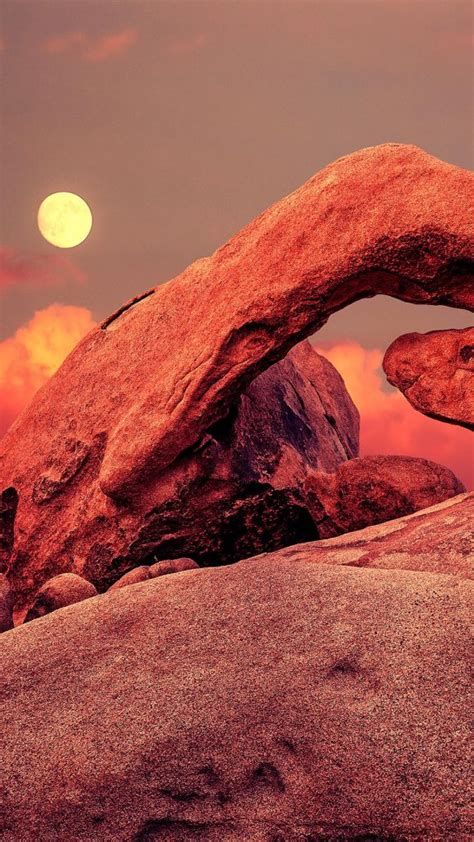 Purple sunset and rising moon over arch in Joshua Tree